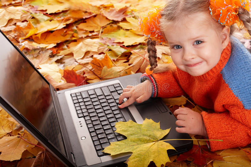 Mädchenkind in der Herbstorange verlässt mit Laptop. lizenzfreie stockfotografie