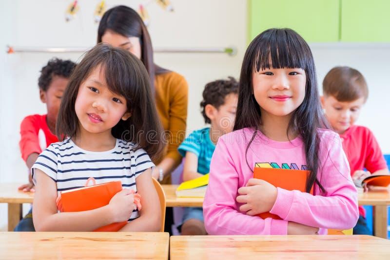 Mädchenkind mit zwei Asiaten, das Buch umarmt und im Klassenzimmer und im whi lächelt stockbild