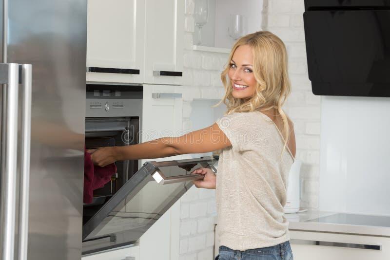 Mädchenkoch mit Ofen mit großem Lächeln lizenzfreies stockfoto