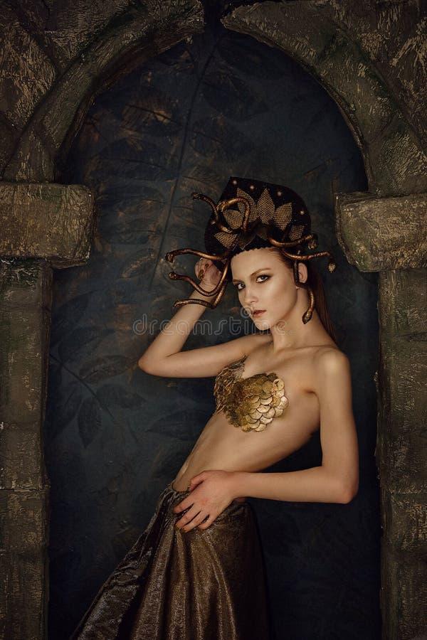 Mädchenkostüm-Quallen gorgon mit Goldbh von den Skalen in einem Steinbogen lizenzfreies stockbild