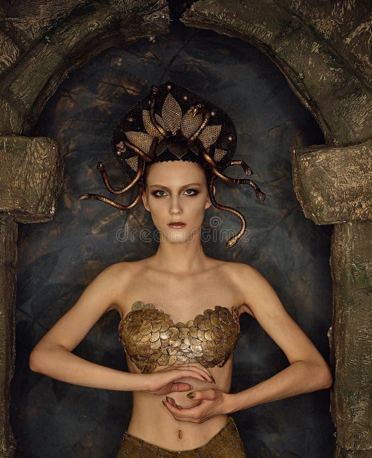 Mädchenkostüm-Quallen gorgon mit Goldbh von den Skalen in einem Steinbogen stockfoto