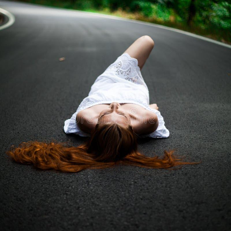 Mädchenlüge auf einer Straße - per Anhalter fahrend stockfotos