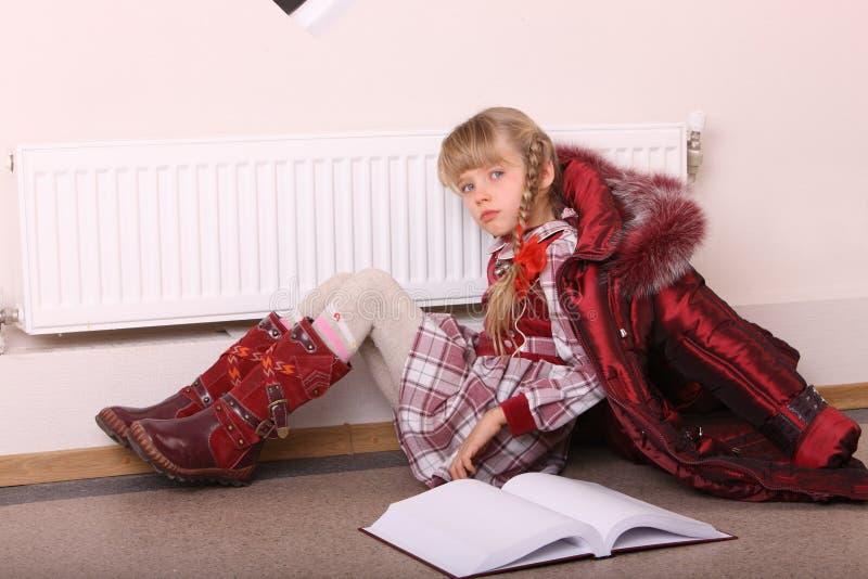 Mädchenlüge auf Fußboden nahe Kühler mit Buch. lizenzfreies stockfoto