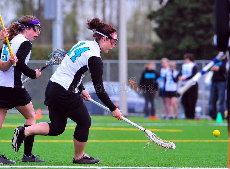 MädchenLacrossespieler nach der Kugel lizenzfreie stockfotos