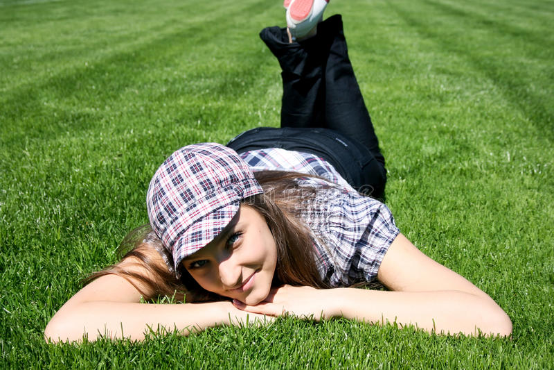 Mädchenlagen auf dem grünen Gras stockbilder