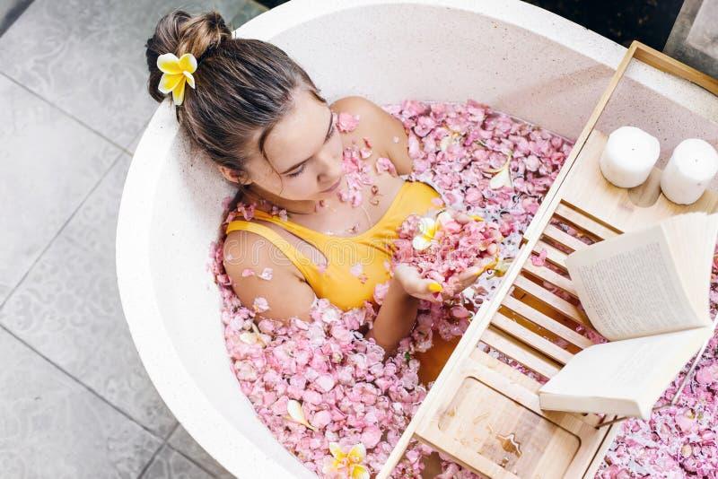 Mädchenlesebuch bei der Entspannung im Whirlpool mit Blumen lizenzfreie stockbilder