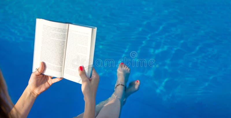 Mädchenlesung durch den Swimmingpool lizenzfreie stockfotografie