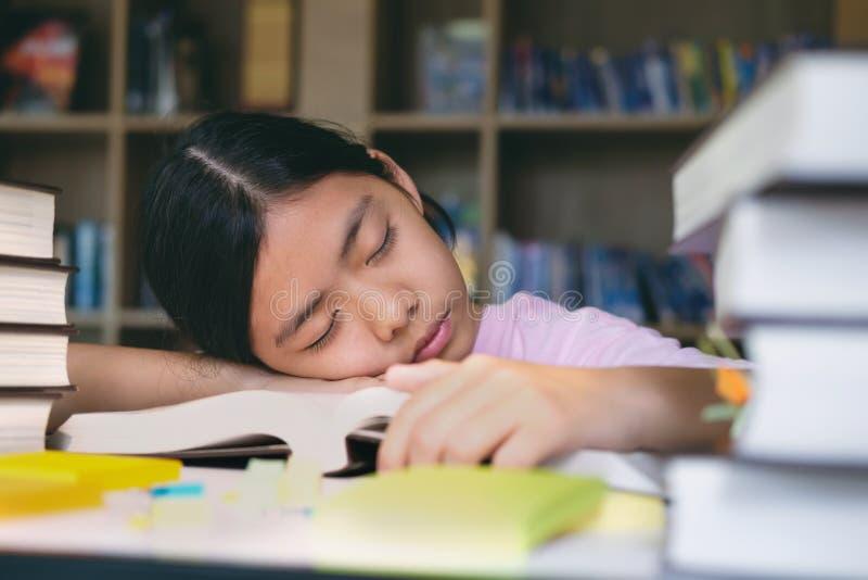 Mädchenlesung und -schreiben und tun Hausarbeit in der Bibliothek stockbild
