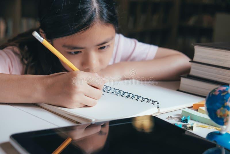 Mädchenlesung und -schreiben und tun Hausarbeit in der Bibliothek lizenzfreies stockbild