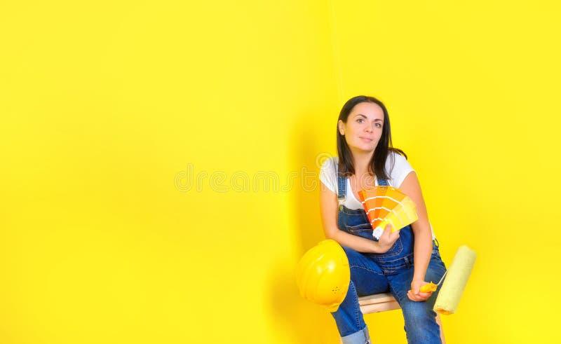Mädchenmaler mit einer Rolle in seinem Sturzhelm sitzt nahe einer gemalten Wand mit einer Palette von Farbwahlen lizenzfreies stockbild