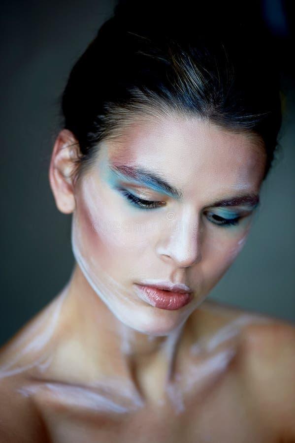 Mädchenmodell mit kreativem Make-up, Farbenanschläge auf dem Gesicht Kreative Person Lebende Skulptur Schauen Sie unten lizenzfreie stockfotografie