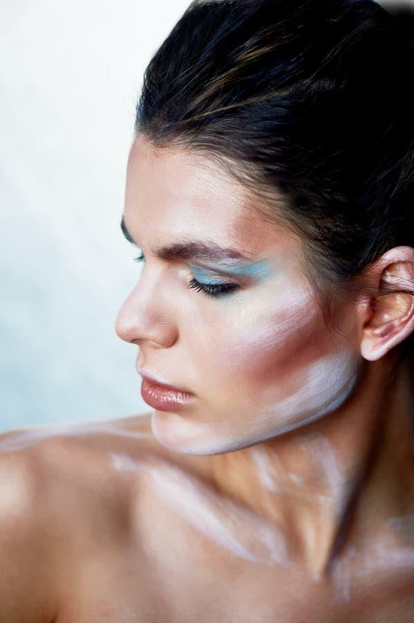 Mädchenmodell mit kreativem Make-up, Farbenanschläge auf dem Gesicht Kreative Person Schauen zur Seite Schulter angehoben lizenzfreies stockbild