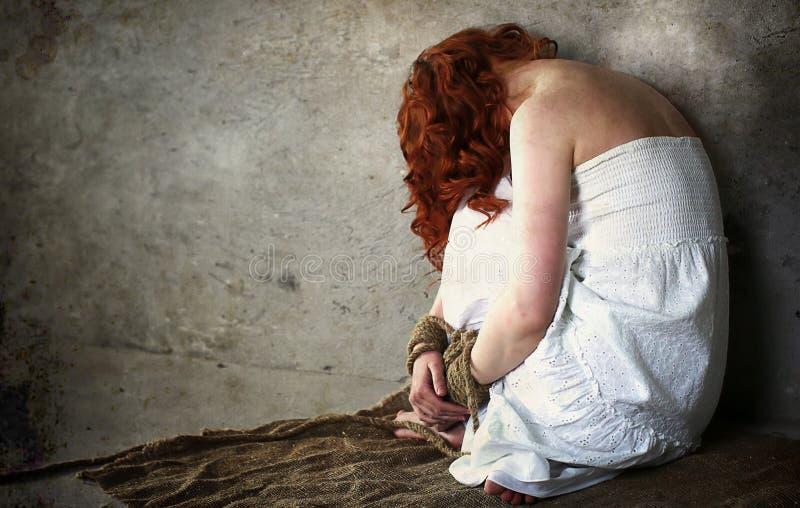 Mädchenopfer der Entführung sitzt gebunden auf dem Boden lizenzfreies stockfoto