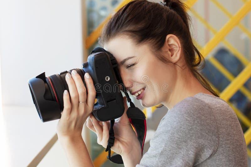 Mädchenphotograph untersucht seine Kamera und schießt etwas stockfoto