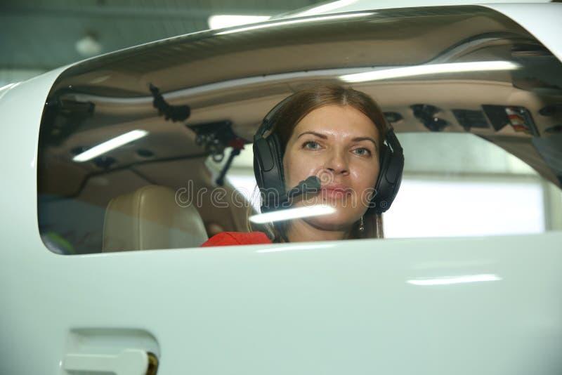 Mädchenpilot schaut heraus das Sportflugzeugfenster stockbild
