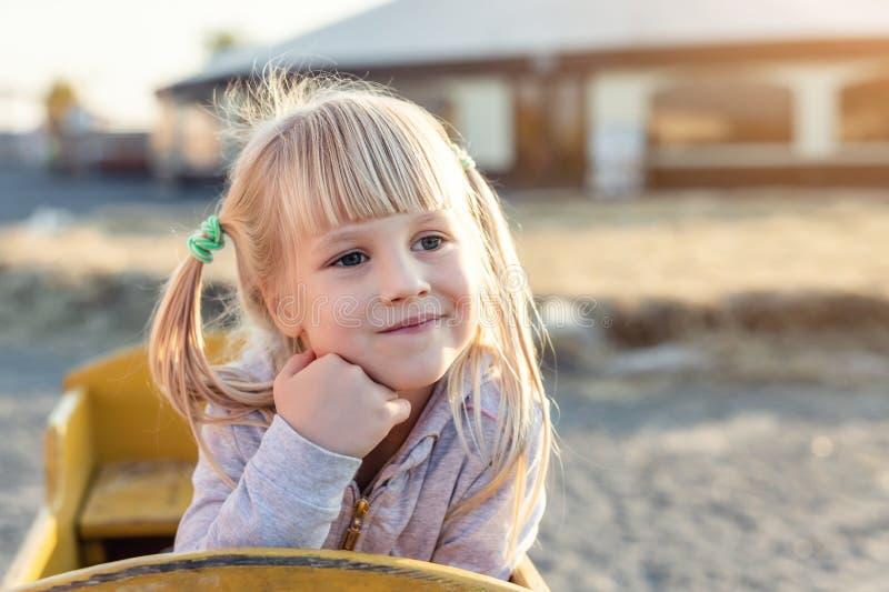 Mädchenporträt des entzückenden netten Kaukasiers blondes Kinder, dasim hölzernen Wagen sitzt, beiseite schaut und am Bauernhof o lizenzfreie stockfotografie