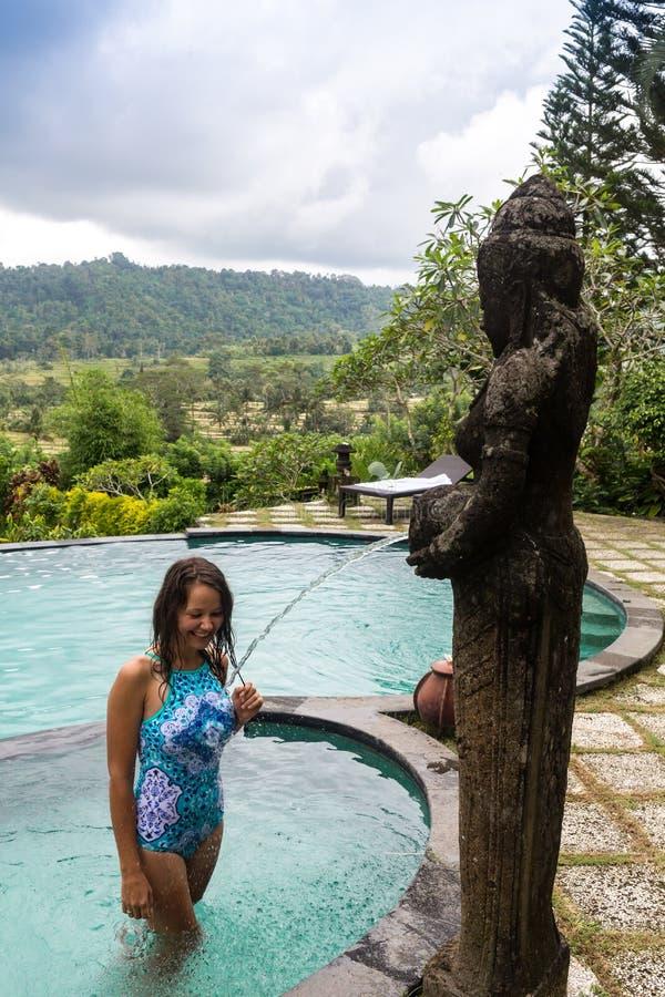 Mädchenporträtaufenthalt draußen darunter in den Regentropfen des tropischen Waldes stockfotografie