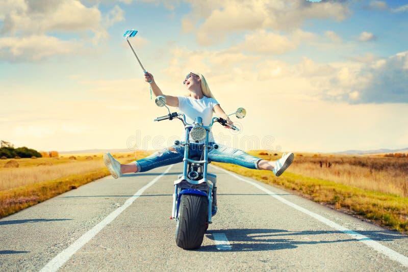 Mädchenradfahrer, der ein Motorrad auf eine Asphaltstraße und fotografiert reitet lizenzfreie stockfotos
