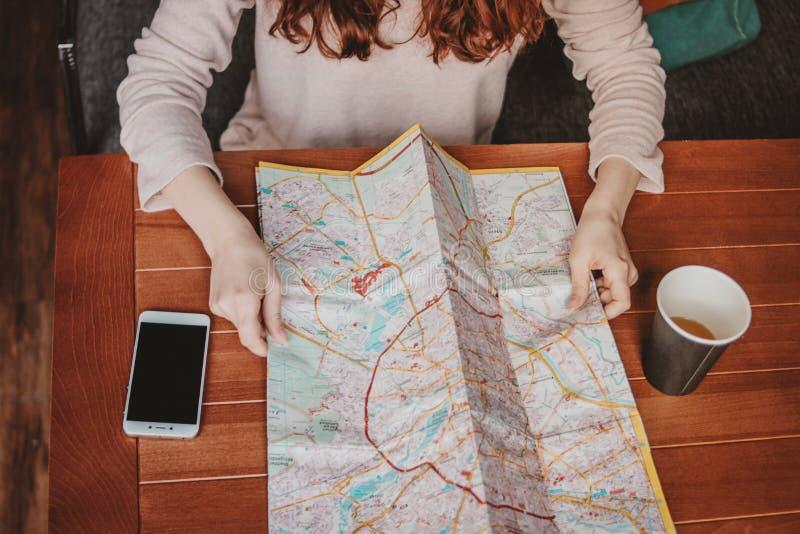 MÄDCHENreisendlesung der jungen Frau rote Haupt, diePapierkarte im Café betrachtet lizenzfreie stockfotografie