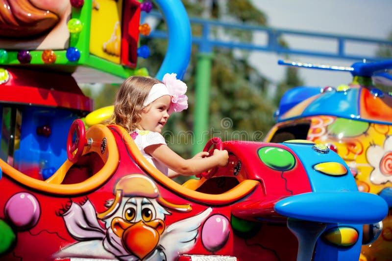 Mädchenreiten auf einem Karussell lizenzfreie stockbilder