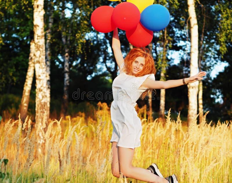 M?dchenrothaarige, die mit Ballons an den gelben ?hrchen springt lizenzfreie stockbilder