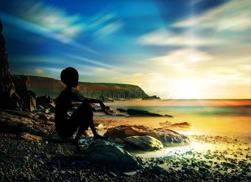Mädchenschattenbild, das allein auf Felsen, Steine auf Ufer des Wassers sitzt lizenzfreie stockfotos