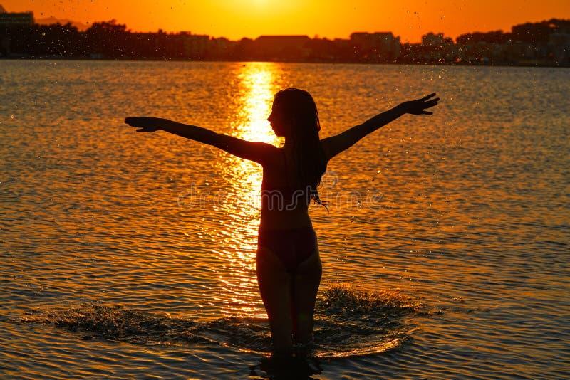 Mädchenschattenbild an den offenen Armen des Strandsonnenuntergangs stockfotografie