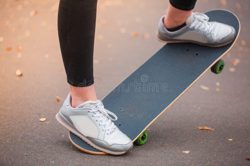 Mädchenschlittschuhläufererhöhungen die Front des Skateboardabschlusses oben stockfoto