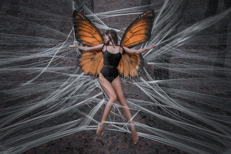 Mädchenschmetterling gegen rote Flügel in einem schwarzen Bodysuitwald lizenzfreies stockbild