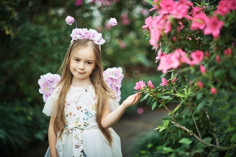 Mädchenschnüffelnblumen von Azaleen blühende Azaleen im Park lizenzfreies stockbild