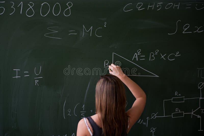 Mädchenschreiben auf der Tafel stockbilder