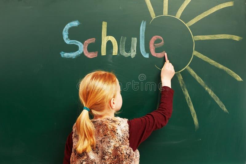 Mädchenschreiben auf der Tafel lizenzfreie stockbilder