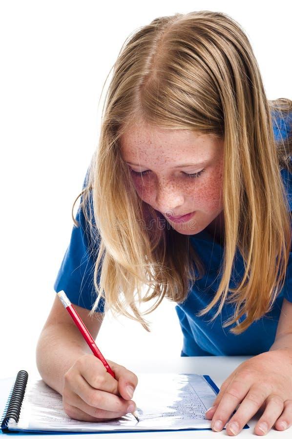 Mädchenschreiben auf Papier stockbilder