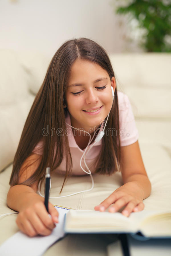 Mädchenschreiben in einem Notizbuch, das auf dem Bett liegt lizenzfreie stockbilder
