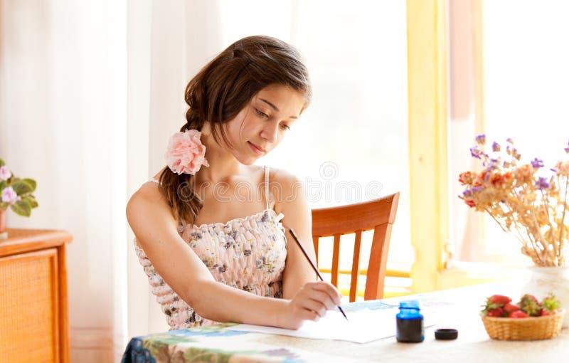Mädchenschreiben am Tisch durch Federinnen stockbild