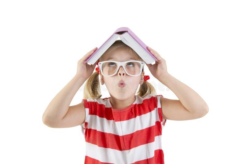 Mädchenschulmädchen, das Buch und das Lächeln hält lizenzfreie stockfotos