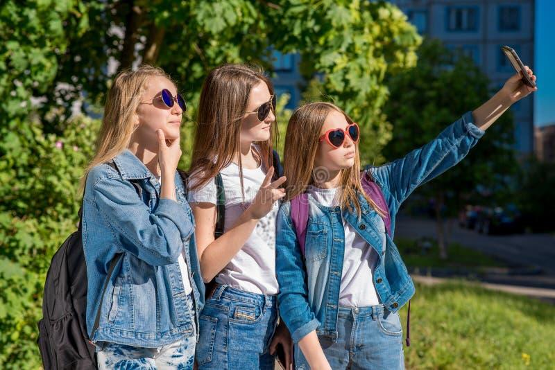 Mädchenschulmädchen im Sommer im Park Er macht Fotos von am Telefon Glückliche lächelnde Haltung auf Kamera Im Denim stockfoto