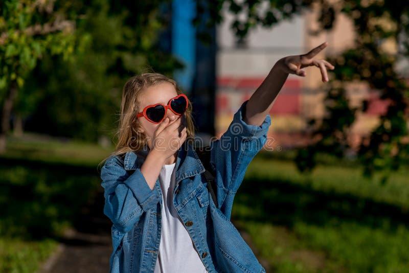 Mädchenschulmädchen Sommer in der Natur Sonnenbrille in Form des Herzens Finger seine Handpunkte zur Seite Das Konzept von stockfotografie