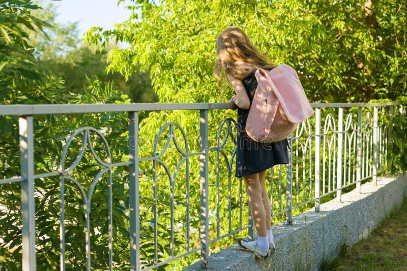Mädchenschulmädchenblondine mit Rucksack in der Schuluniform nahe Zaun im Schulhof, zurück zu Schule lizenzfreie stockfotos