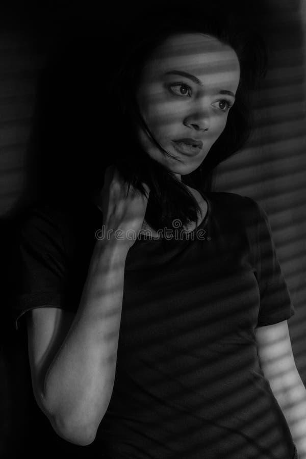 Mädchenschwarzweiss-Foto Schwarzes Weiß Stand im Schatten des hellen Spiels das Mädchen an den Jalousien lizenzfreie stockfotos
