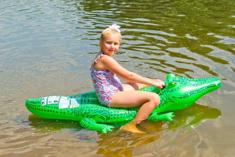 Mädchenschwimmen im Fluss mit aufblasbarem Krokodil stockfotos