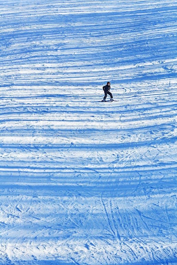 Mädchenskifahren auf den schneebedeckten Steigungen des späten Nachmittages mit transversalem stockbilder