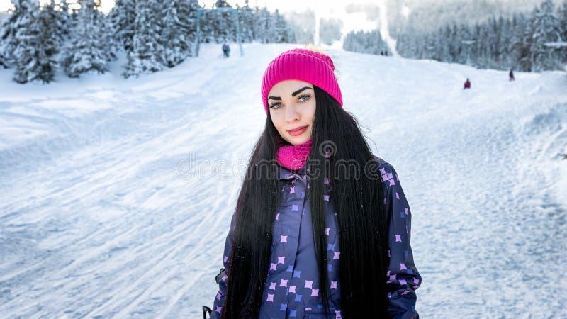 Mädchensnowboarder, der im Winter auf der lächelnden und schauenden Skisteigung steht stockfoto