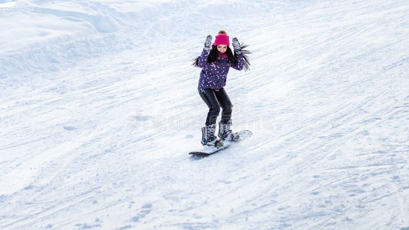 Mädchensnowboarder steigt von den Bergen im Schnee auf einem Snowboard ab lizenzfreie stockbilder