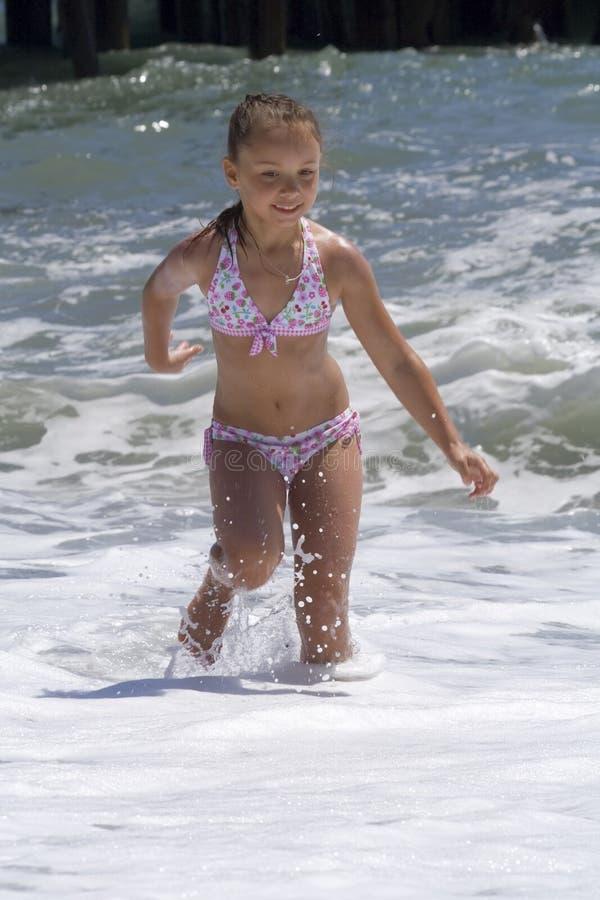 Mädchenspiele an der Küste lizenzfreie stockbilder