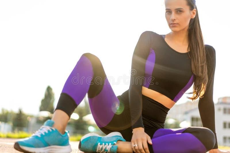 Mädchensportler crossfit und Hocken agains bei Sonnenuntergang im stadi lizenzfreies stockfoto