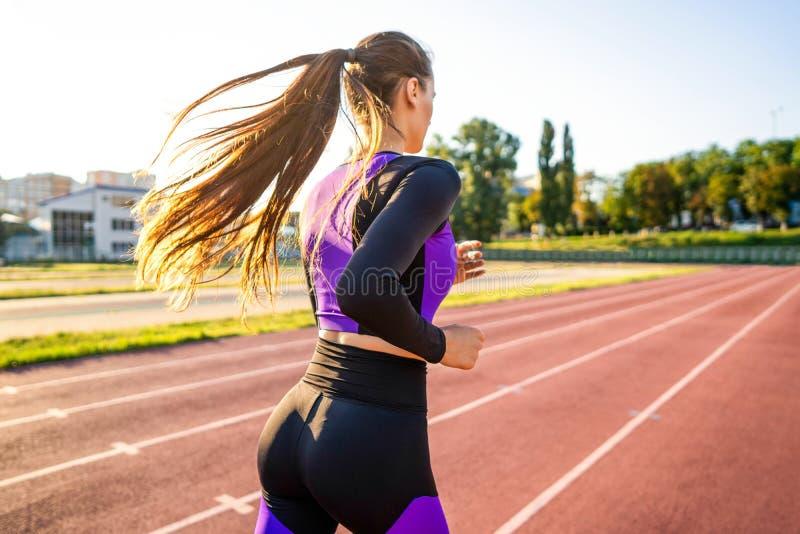 Mädchensportler crossfit und Hocken agains bei Sonnenuntergang im stadi stockbild