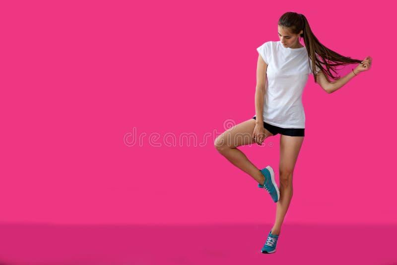 Mädchensportler, der auf einem rosa Hintergrund aufwirft lizenzfreie stockfotos