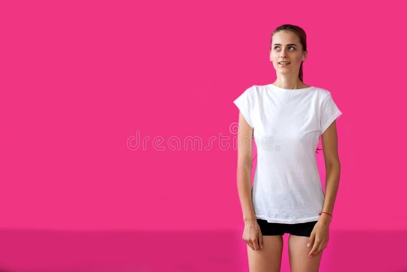 Mädchensportler, der auf einem rosa Hintergrund aufwirft stockbild