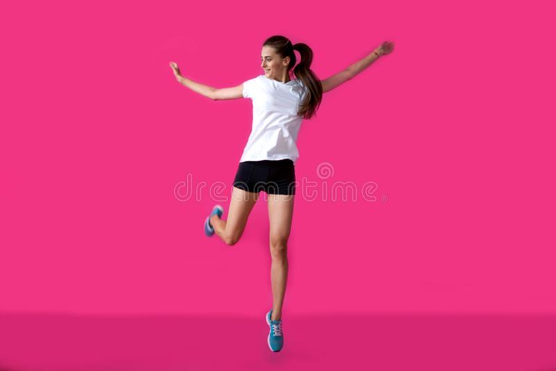 Mädchensportler, der auf einem rosa Hintergrund aufwirft stockfotografie